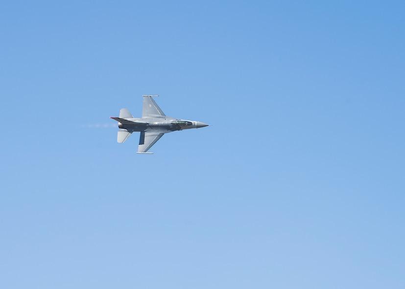 A F-16 flying above Misawa Air Base performing aerial maneuvers.