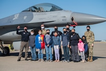Group of Civil Air Patrol and U.S. Air Force members stand in front of an F-16 Fighting Falcon for a photo.