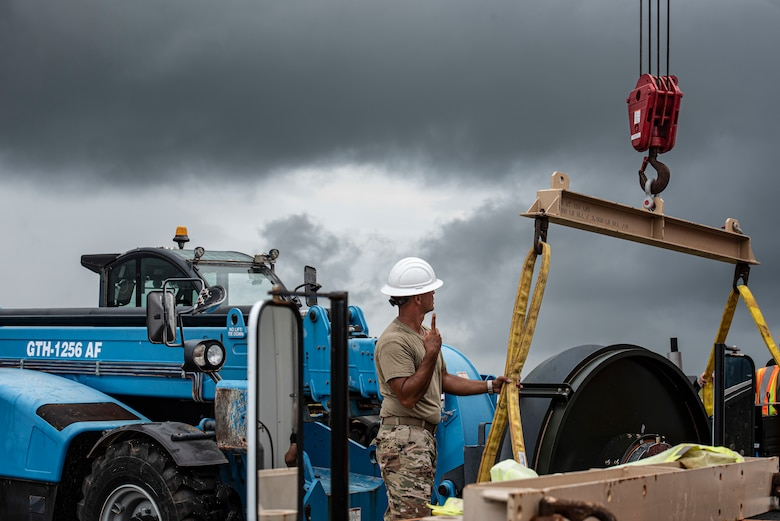 U.S. Air Force Master Sgt. Jeremy Lawson, 36th Civil Engineer Squadron heavy repair section chief, signals to a crane operator to lift the new Barrier Arresting Kit on the flight line at Andersen Air Force Base, Guam, April 26, 2021.