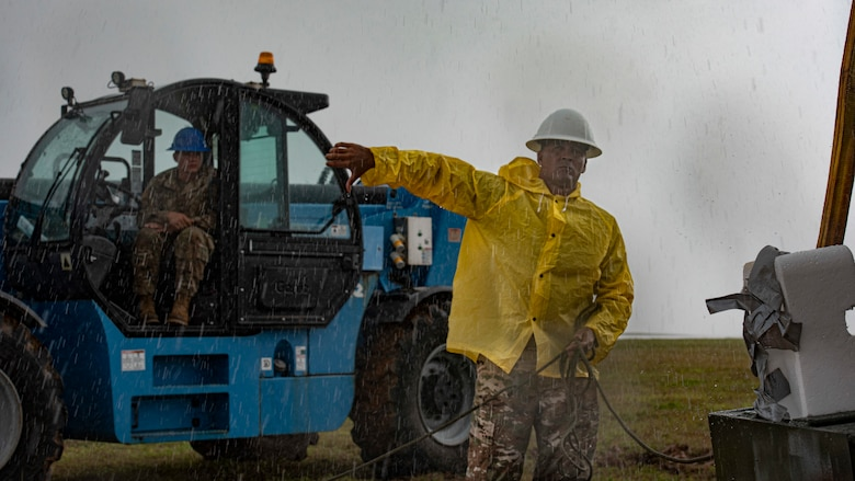 U.S. Air Force Master Sgt. Jeremy Lawson, 36th Civil Engineer Squadron heavy repair section chief, carries a trail line in the rain on Andersen Air Force Base, Guam, April 26, 2021.