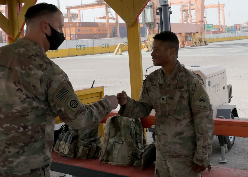Army Reserve Brig. Gen. Justin M. Swanson, the deputy commanding general of the 1st Theater Sustainment Command, fist pumps Spc. Demarcus Russ after the general's April 24, 2021 tour of port operation at Kuwait's Port Shuaiba. The general was thanking Soldiers for providing security during offload and onload operations, when the New Orleans native learned that the specialist with the 1st Armored Division Soldier grew up in Jonesville, Louisiana.