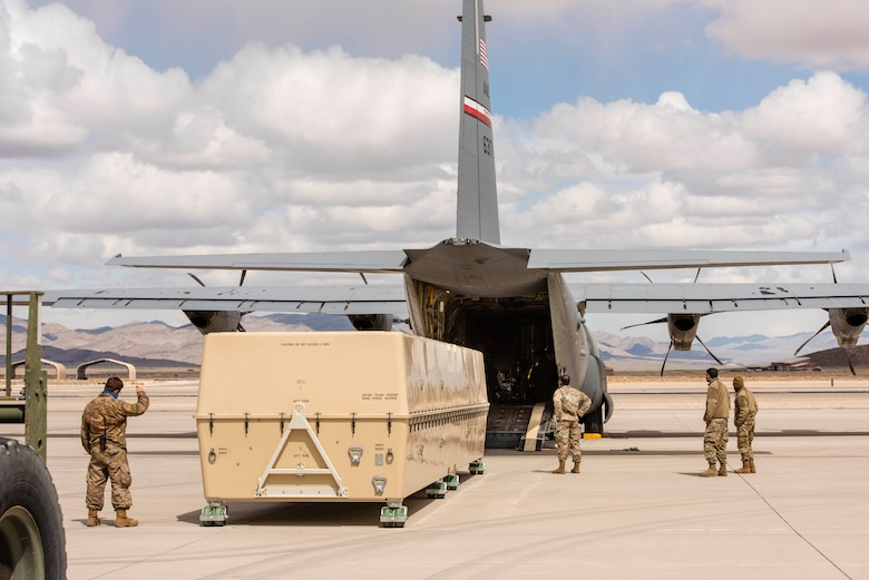 Airmen use a two ton fork lift puts an MQ-9 Reaper onto a C-130 for transport.