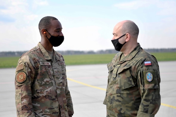 U.S. Air Force Tech. Sgt. John Wilson, 52nd Operations Group Detachment 1 maintenance support liason, chats with Polish Air Force Maj. Wojciech Adamczyk, 32nd Air Base flight safety inspector, at Łask Air Base, Poland, April 21, 2021. Some of Wilson's duties include working with the Polish Air Force to resolve maintenance issues and conduct inspections. (U.S. Air Force photo by Tech. Sgt. Warren D. Spearman Jr.)