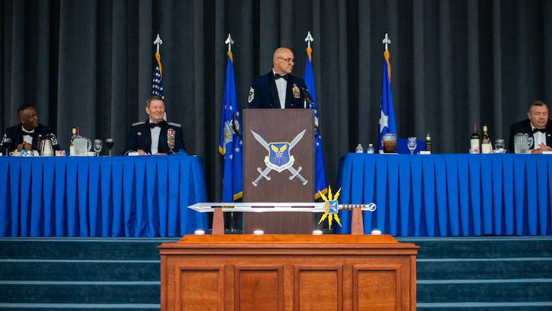 Chief Master Sgt. Robert Tibi, center, Air Force Global Strike Command command first sergeant, makes remarks during the Order of the Sword ceremony honoring retired Gen. Robin Rand, second from left, former AFGSC commander, at Barksdale Air Force Base, Louisiana, April 23, 2021. The Order of the Sword ceremony was patterned after two orders of chivalry founded during the Middle Ages in Europe: the (British) Royal Order of the Sword and the Swedish Military Order of the Sword, still in existence today. (U.S. Air Force photo by Airman 1st Class Jacob B. Wrightsman)