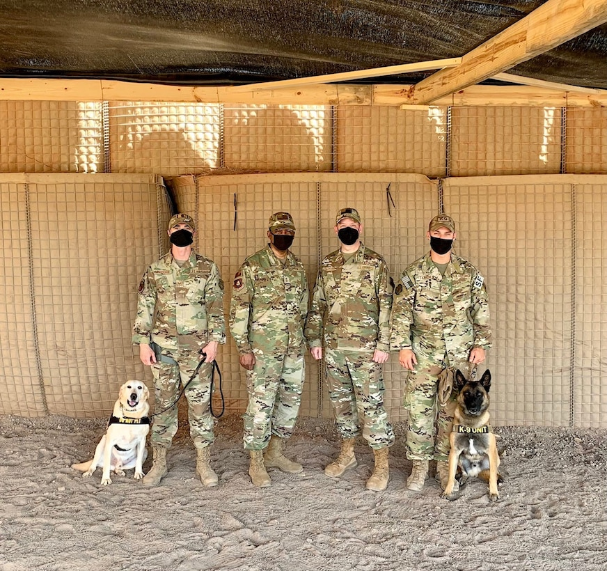 U.S. Air Force Staff Sergeants Dakota Farrow and Patrick Saddoris, 726th Expeditionary Air Base squadron military working dog handlers, pose with Maj. Gen. Randall Reed, Third Air Force commander, and Chief Master Sergeant Randy Kwiatkowski, Third Air Force command chief, at Camp Chabelley, Djibouti, April 15, 2021. Third Air Force leadership conducted a visit to the new working dog compound while conducting visits at Camp Lemonnier and Chabelley.  (Courtesy photo by Maj. Tim O'Rouke)