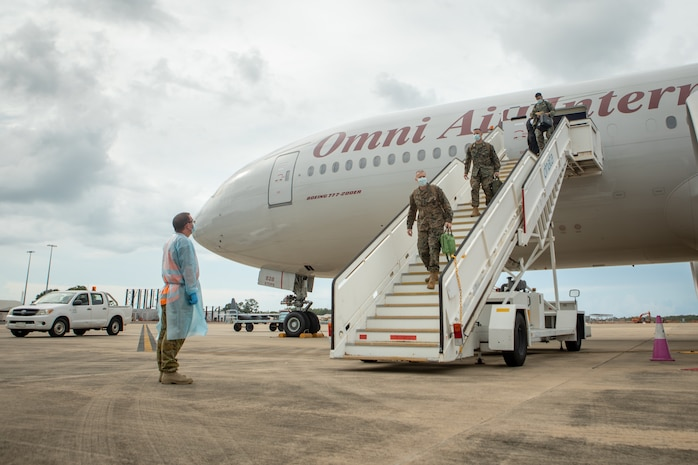 Australian Army Warrant Officer Class 2 Lee Pendlebury, left, an operations warrant officer with Marine Rotational Force – Darwin, prepares to assist U.S. Marines with MRF-D, at Royal Australian Air Force Base, Darwin, NT, Australia, March 22, 2021. Marines and Sailors with MRF-D are required to conduct strict COVID-19 mitigation procedures prior to arrival in Darwin, in compliance with Northern Territory Health Authorities. All service members must provide three documented negative COVID-19 swab tests throughout their travel and prior to being released from a 14-day quarantine period. (U.S. Marine Corps photo by Sgt. Micha Pierce)