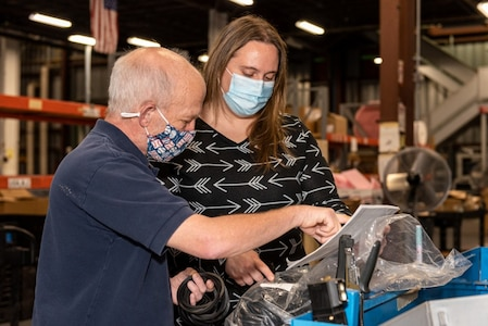 Photo of a woman and a man are in a warehouse area looking at documentation.