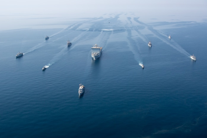 """210421-A-BD272-0073 ARABIAN GULF (April 21, 2021) - A multinalional group of mine countermeasure ships from the French Marine Nationale, UK Royal Navy, U.S. Navy and a MH-53E Sea Dragon helicopter, attached to the """"Blackhawks"""" of Helicopter Mine Countermeasures Squadron (HM-15), operate in formation during exercise Artemis Trident 21 in the Arabian Gulf, April 21. Artemis Trident 21 is a multilateral mine countermeasures exercise between the UK, Australia, France and U.S., designed to enhance mutual interoperability and capabilities in mine hunting and clearance, maritime security and dive operations, allowing participating naval forces to effectively develop the necessary skills to address threats to regional security, freedom of navigation and the free flow of commerce. (U.S. Army photo by Spc. Theoren Neal)"""