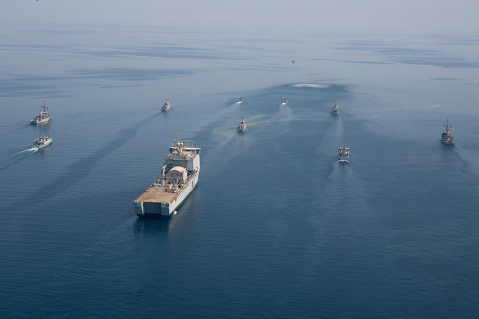 """210421-A-BD272-0418 ARABIAN GULF (April 21, 2021) - A multinalional group of mine countermeasure ships from the French Marine Nationale, UK Royal Navy, U.S. Navy and a MH-53E Sea Dragon helicopter, attached to the """"Blackhawks"""" of Helicopter Mine Countermeasures Squadron (HM-15), operate in formation during exercise Artemis Trident 21 in the Arabian Gulf, April 21. Artemis Trident 21 is a multilateral mine countermeasures exercise between the UK, Australia, France and U.S., designed to enhance mutual interoperability and capabilities in mine hunting and clearance, maritime security and dive operations, allowing participating naval forces to effectively develop the necessary skills to address threats to regional security, freedom of navigation and the free flow of commerce. (U.S. Army photo by Spc. Theoren Neal)"""