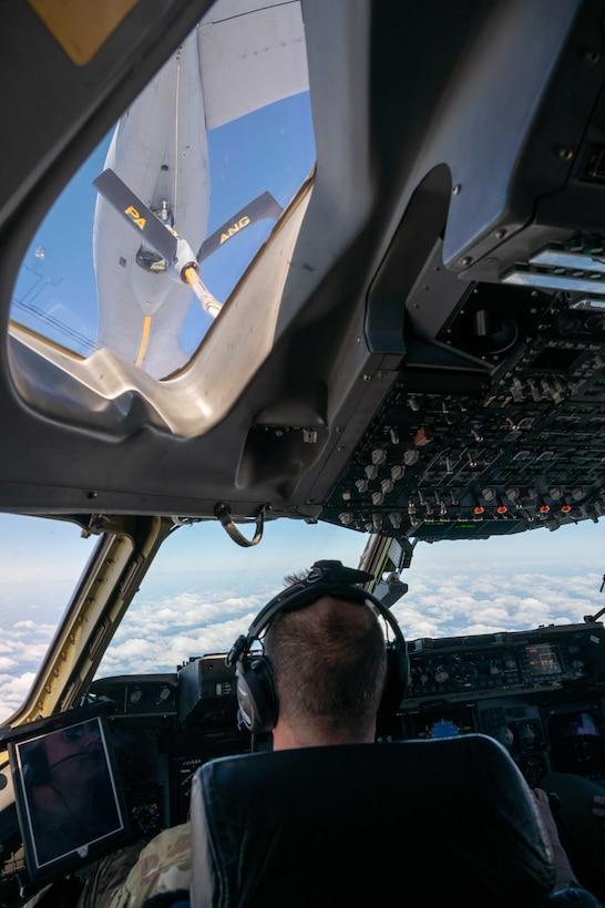 Maj. James Johnson, 3rd Airlift Squadron pilots, prepares a C-17 Globemaster III for an aerial refueling from a 171st Air Refueling Wing KC-135 Stratotanker, assigned to the  Pennsylvania Air National Guard, over Ohio, April 22, 2021. The 3rd AS trains to support global engagement through direct delivery of critical theater assets and to ensure combat readiness of Air Mobility Command C-17 aircrews. (U.S. Air Force photo by Airman 1st Class Faith Schaefer)
