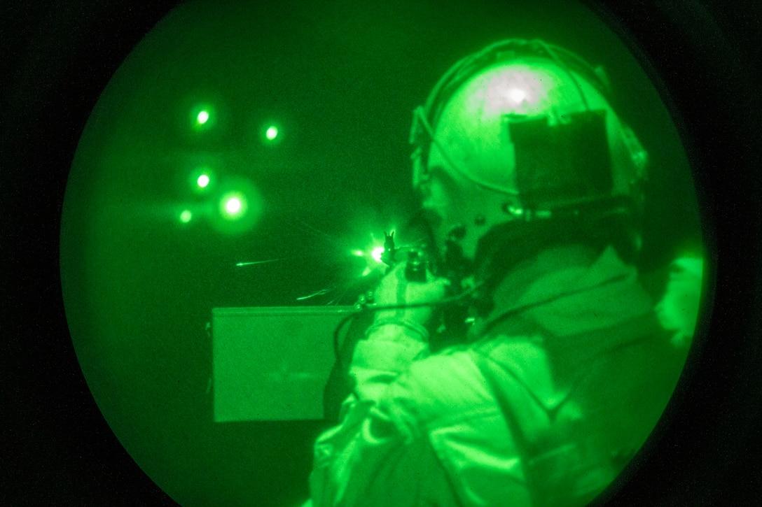 A U.S. Marine fires an M240D 7.62 mm machine gun, during a night gun range near Yuma, Ariz.,April21.
