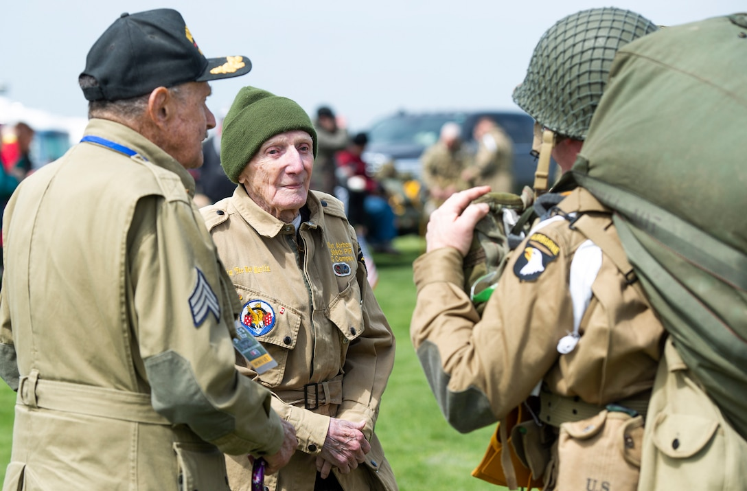 """WWII veterans, Dan McBride and Jim """"Pee Wee"""" Martin, greet members of a WWII airborne demonstration team as they leave the drop zone during a 100th birthday celebration held in Martin's honor, April 23, 2021, in Xenia, Ohio. Both McBride and Martin, served as paratroopers assigned to 101st Airborne Division out of Fort Campbell, Kentucky. (U.S. Air Force photo by Wesley Farnsworth)"""