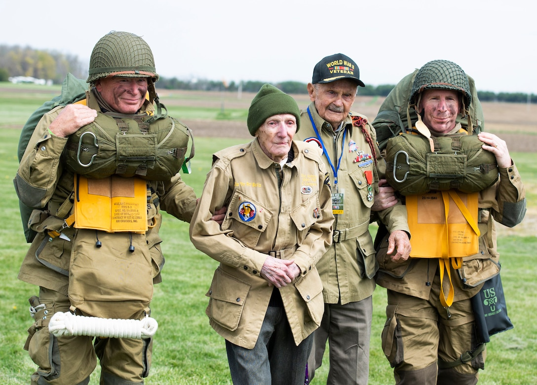 """WWII airborne demonstration team members walk with WWII veterans, Dan McBride, center left, and Jim """"Pee Wee"""" Martin, center right, as they exit the drop zone during a 100th birthday celebration held in Martin's honor, April 23, 2021, in Xenia, Ohio. Both McBride and Martin, served as paratroopers assigned to 101st Airborne Division out of Fort Campbell, Kentucky. (U.S. Air Force photo by Wesley Farnsworth)"""