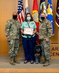 General Brig. Gen. Shan Bagby and Command Sgt. Maj. Thurman Reynolds present Kris Blair and therapy dog Huckleberry a certificate of appreciation for their volunteer service.