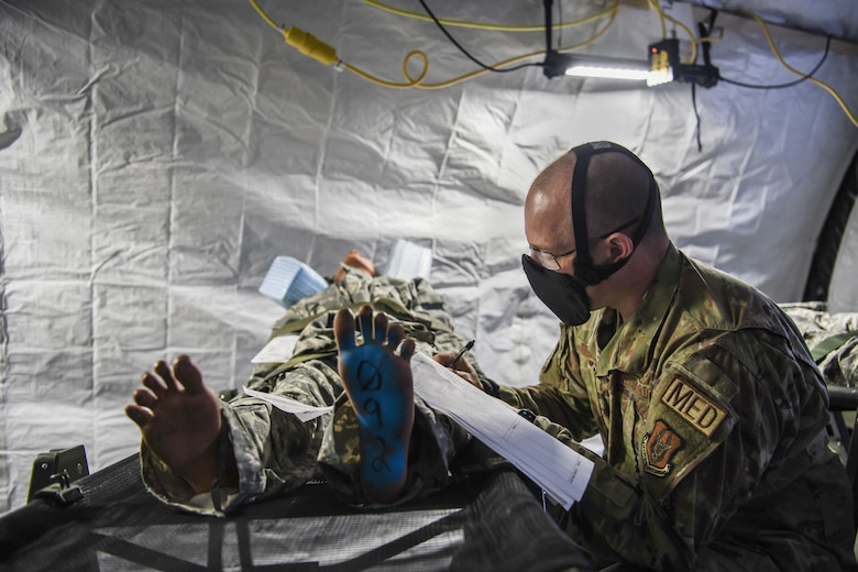 First Lieutenant Tyler Trease, 445th Aeromedical Staging Squadron clinical nurse and officer in-charge of exercise planning and safety, reviews a patient's medical documentation during Ultimate Caduceus training exercise April 28, 2021.  U.S. Transportation Command (USTRANSCOM) began the week-long aeromedical and global patient movement exercise April 26. Approximately 250 personnel including members of the 445th Airlift Wing and the 88th Air Base Wing participated in the field training exercise. The exercise simulates bringing in injured troops from overseas, triaging them to Wright-Patterson Air Force Base and then moving them to longer-term and advanced care centers known as Federal Coordinating Centers (FCC).  (U.S. Air Force photo/Master Sgt. Patrick O'Reilly)