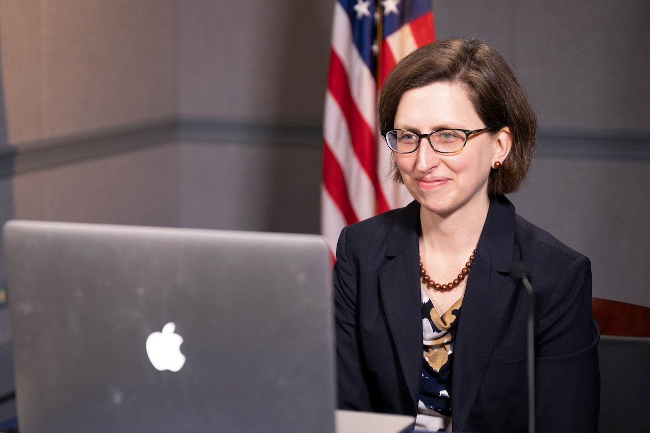 A woman looks at a laptop screen; a U.S. flag is in the background.