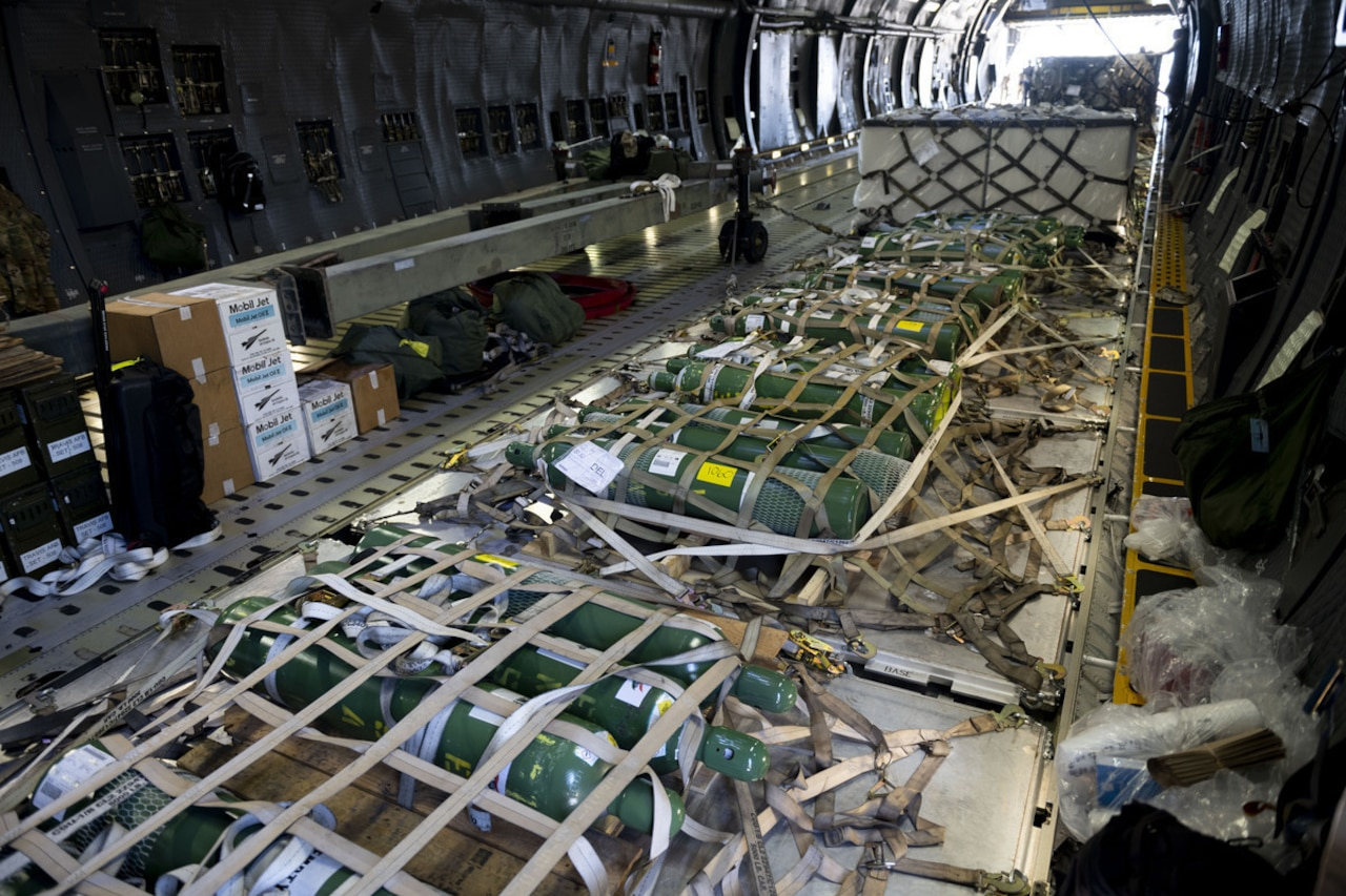 Inside a military aircraft, metal cylinders are attached to the floor with netting.