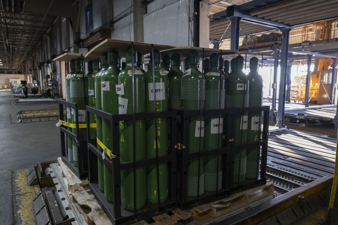 Dozens of metal oxygen cylinders sit on wooden pallets.
