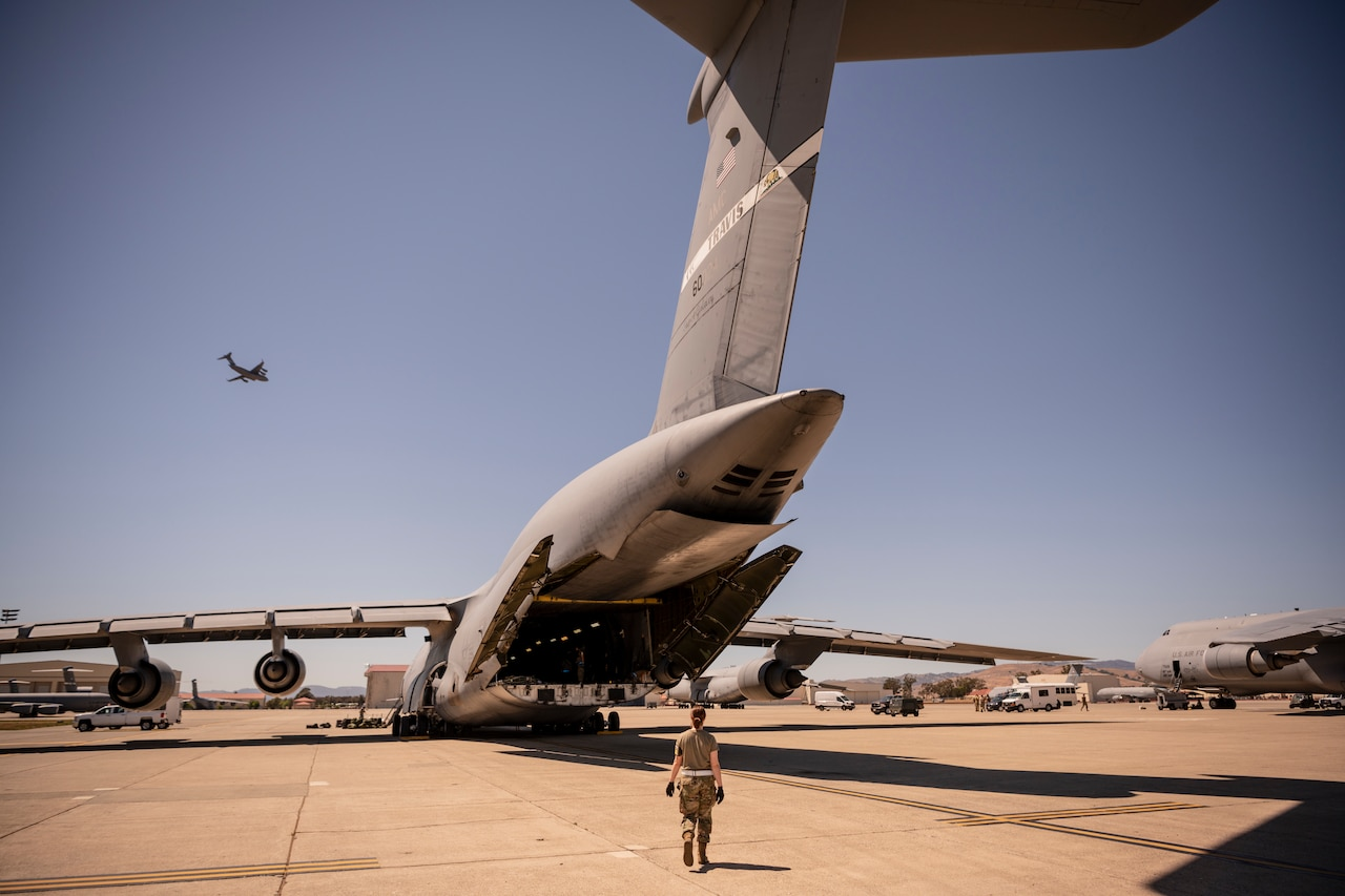 A large military aircraft has its rear loading door open as a woman in a military uniform approaches.