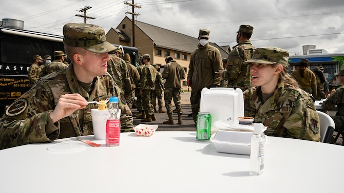 Two Airmen sitting at a table talking and eating.