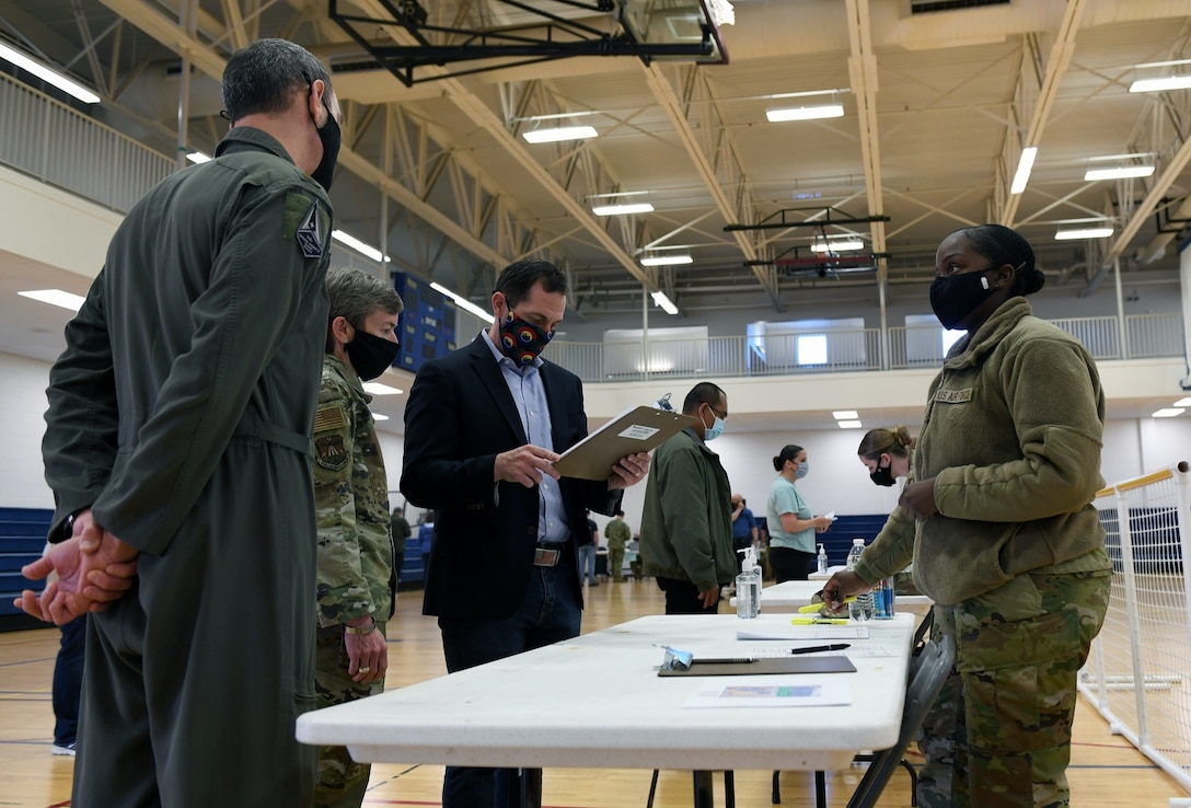 Staff Sgt. Simone Napue, far right, 566th Intelligence Squadron NCO in charge of operations support, explains to Congressman Jason Crow the first step of the vaccine distribution on Buckley Air Force, Colo., April 29, 2021. Crow visited Buckley to see first-hand how the 460th Medical Group operates the vaccine point of dispensing (POD). POD lines allow the Air Force to provide mass vaccinations to the beneficiaries or target population. (U.S. Space Force photo by Airman 1st Class Haley N. Blevins)