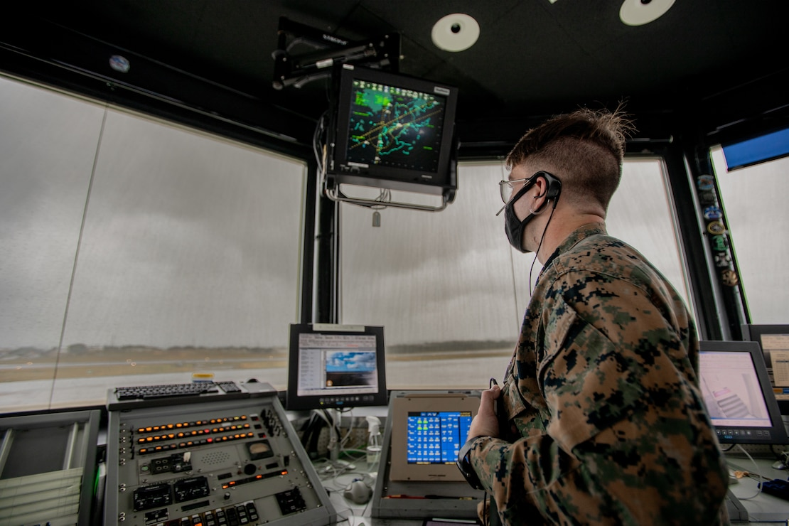 U.S. Marine Corps Lance Cpl. Collin Walton, an air traffic control specialist with Headquarters and Headquarters Squadron, Marine Corps Air Station Futenma, communicates with aircraft on MCAS Futenma, Okinawa, Japan, Jan. 7, 2021. Air traffic controllers aboard MCAS Futenma are responsible for the safe and expeditious flow of air traffic as well as the security of the mission of aviation assets. (U.S. Marine Corps photo by Cpl. Terry Wong)