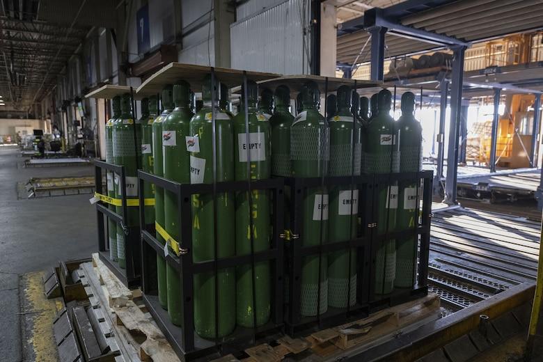 Dozens of metal oxygen cylinders sit on wooden pallets.