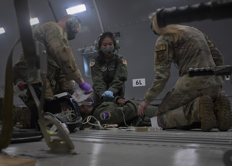 Aeromedical evacuation Airmen perform simulated CPR on a patient during an in-air medical emergency exercise aboard a new KC-46A Pegasus, April 23, 2021. The tanker, from the 916th Air Refueling Wing, was flown by the 77th Air Refueling Squadron, and was used by the aeromedical Airmen to become more familiar with the aircraft and its aeromedical evacuation capabilities. (U.S. Air Force photo by Tech. Sgt. Miles Wilson)