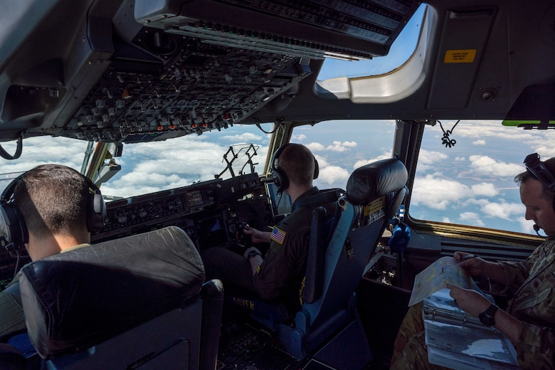 From the left, Capt. Stephen Tice and 1st Lt. Forrest Doss, both 3rd Airlift Squadron pilots, fly a C-17 Globemaster III during a local training flight while Maj. James Johnson, 3rd AS pilot, reviews and discusses a flight plan map over Ohio, April 22, 2021. The 3rd AS trains to support global engagement through direct delivery of critical theater assets and to ensure combat readiness of Air Mobility Command C-17 aircrews. (U.S. Air Force photo by Airman 1st Class Faith Schaefer)