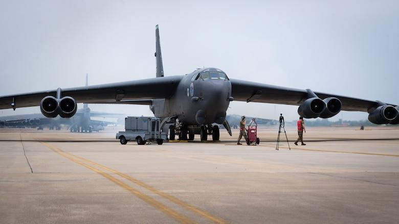 "Senior Airman Ryan Braun and Airman 1st Class Eric Dearment, 96th Aircraft Maintenance Unit crew chiefs, lead a B-52H Stratofortress as it is ""cart started"" at Barksdale Air Force Base, Louisiana, April 28, 2021."