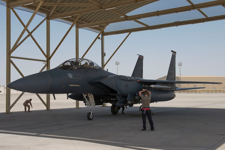 A crew chief assigned to the 380th Expeditionary Aircraft Maintenance Squadron marshals an F-15E Strike Eagle assigned to the 332nd Air Expeditionary Wing (AEW) at Al Dhafra Air Base, United Arab Emirates, April 25, 2021. The 494th Expeditionary Fighter Squadron, assigned to the 332nd AEW, re-located to Al Dhafra Air Base from an undisclosed location in order to support a U.S. Air Forces Central Agile Combat Employment operation. (U.S. Air Force photo by Staff Sgt. Zade Vadnais)