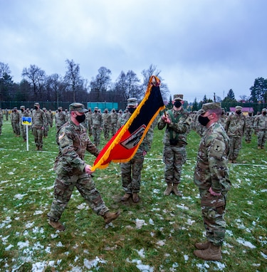Col. James Perrin and Command Sgt. Maj. Carter Richardson unfurl the colors of the 81st SBCT out of Washington State as they take command of the JMTG-U during the TOA ceremony.