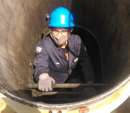 A woman in overalls climbs in to a ship's fuel tank