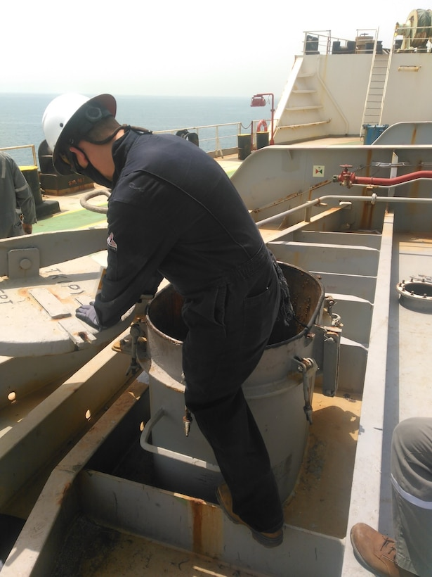 A man in overalls climbs in to a ship's fuel tank