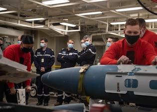 French Armaments Procurements Agency members observe Sailors build a training bomb aboard USS Gerald R. Ford (CVN 78).
