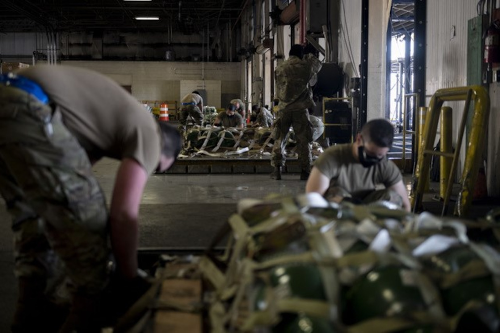 Airmen strap down pallets of cargo with webbing in a warehouse
