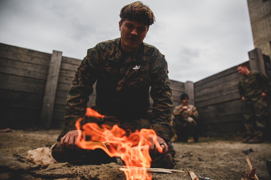 A U.S. Marine builds a fire for an ammunition burn at Koth Demolition Range in Rota, Spain, April 24.