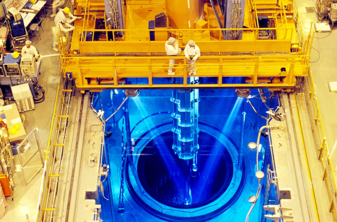 Fuel rods being loaded into a nuclear power station's reactor core. The reactor itself is immersed beneath the water (blue), and lifting machinery is being used to raise and lower the fuel rods (centre) into the core (circular area).