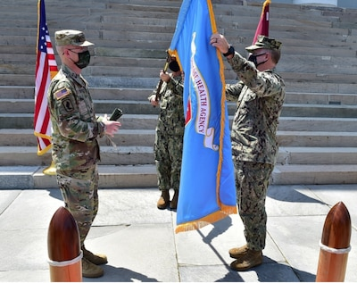 U.S. Army Lt. Gen. Ronald Place, director of the Defense Health Agency, left, and U.S. Navy Rear Adm. Darin K. Via, director of the Tidewater Market, and commander, Naval Medical Forces Atlantic, unfurl the Defense Health Agency flag during a socially distanced establishment ceremony to mark the standup of the Tidewater Market, April 28, 2021.