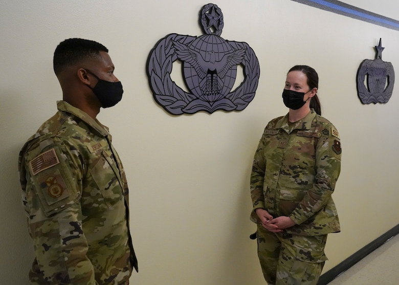 U.S. Air Force Senior Master Sgt. Travis Jordan, 81st Security Forces Squadron operation superintendent, helps Staff Sgt. Jessica Arceneaux, 81st SFS commander support staff NCO in charge inside the security forces building at Keesler Air Forces Base, Mississippi, April 29, 2021. Jordan serves as a mentor for the Airmen in his unit.