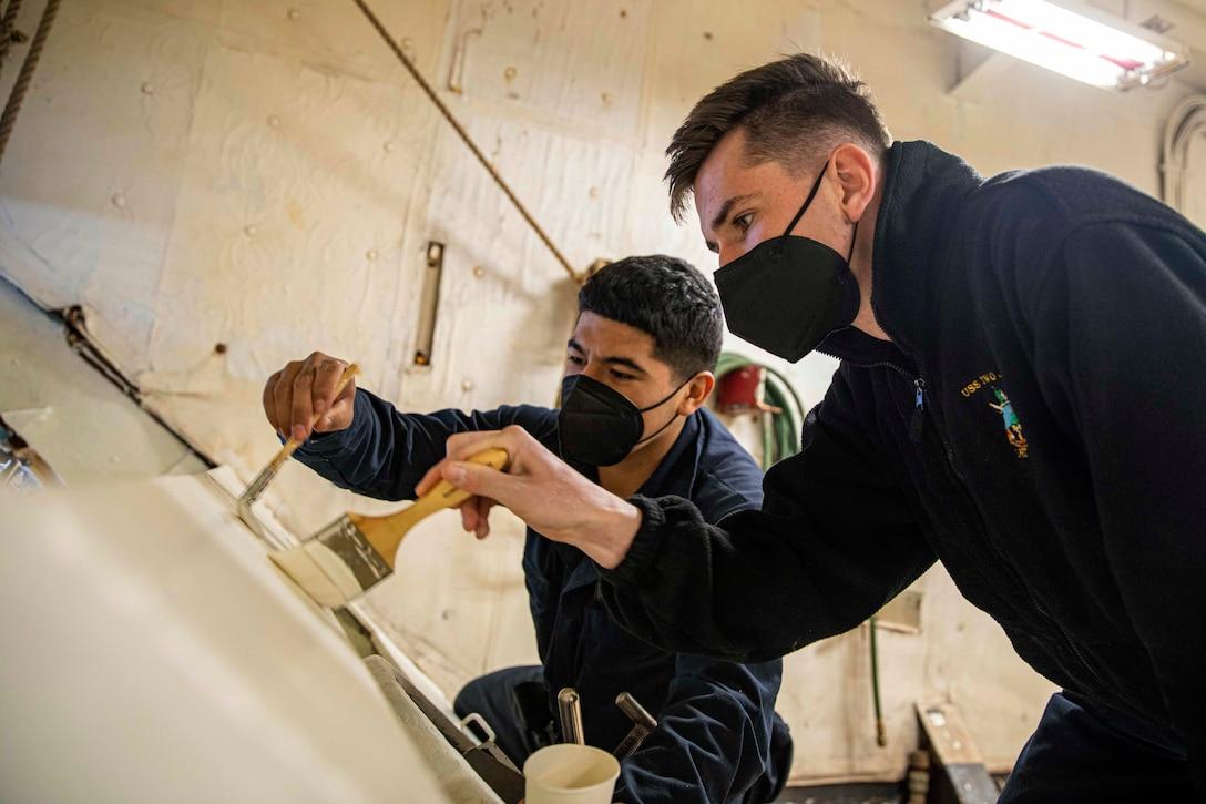 Two sailors paint part of a ship.