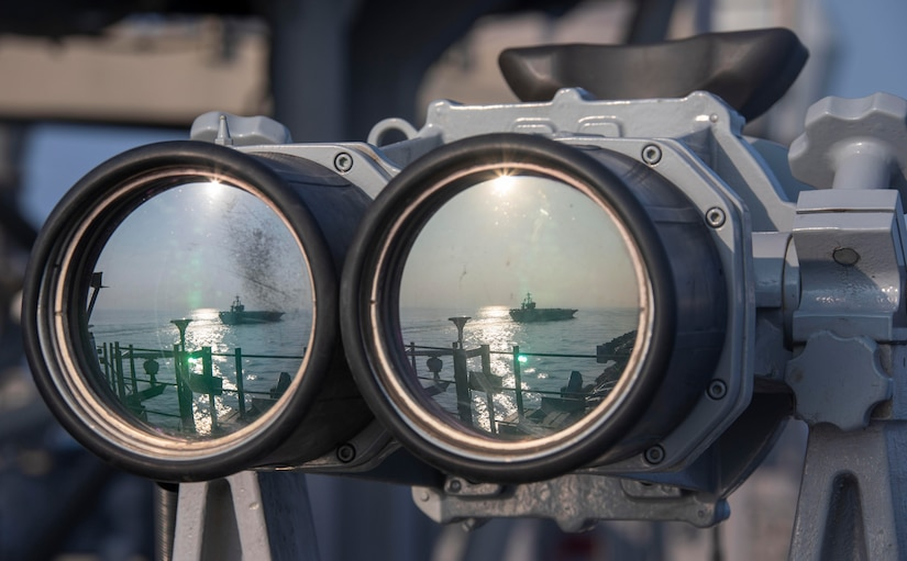 The reflection of a ship at sea shows on the lenses of a pair of binoculars.
