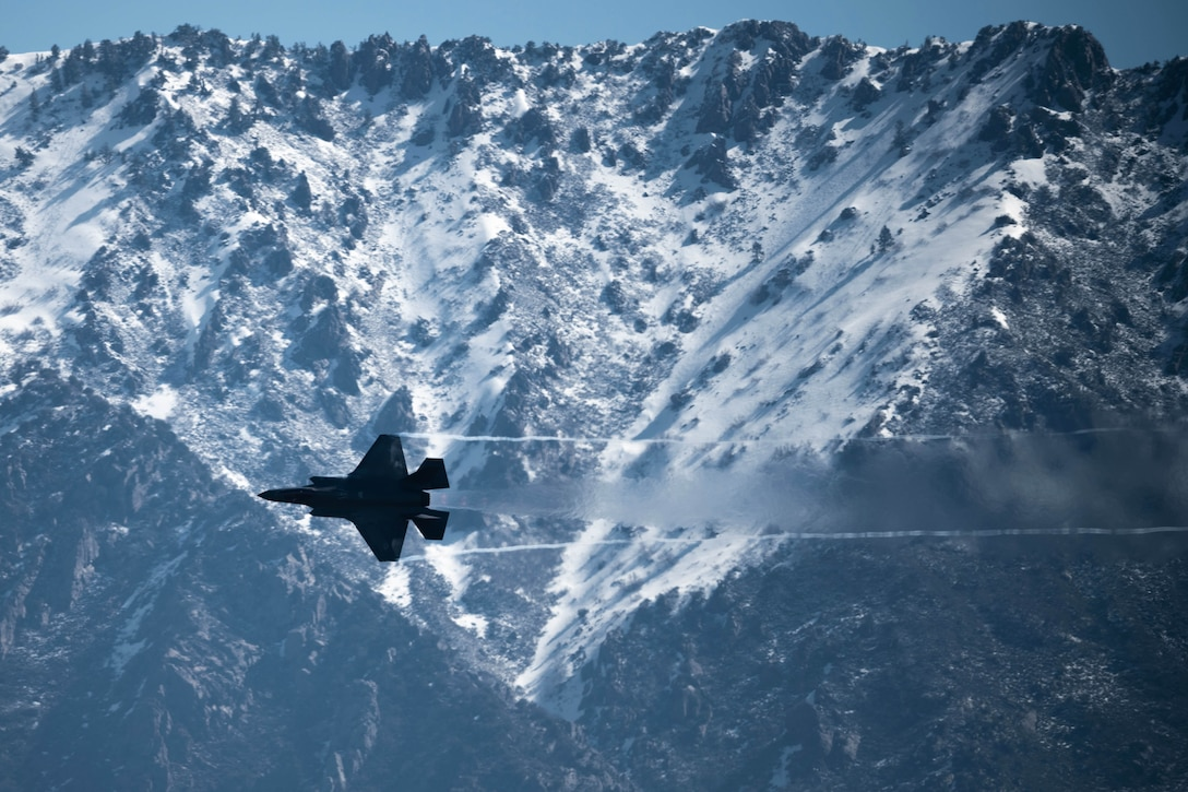 An aircraft flies by snowy mountains.