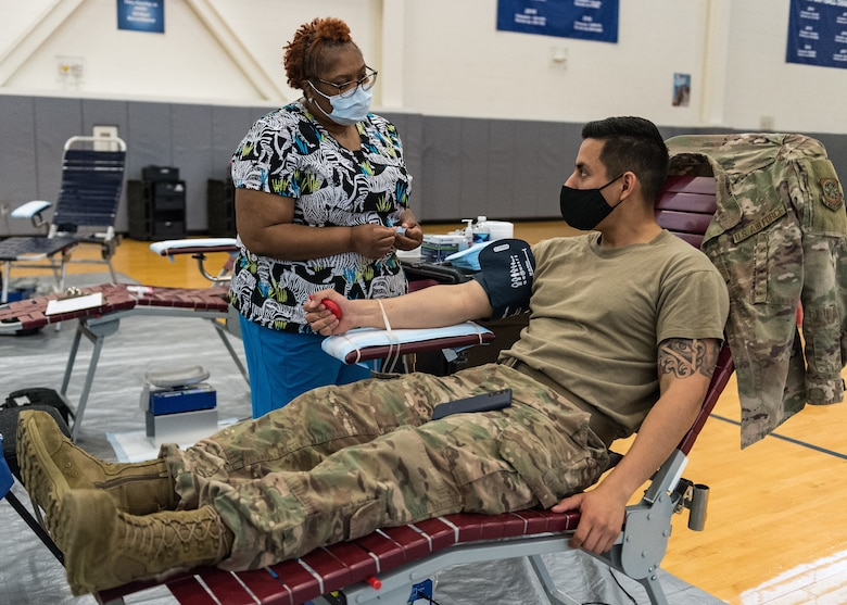 Monica Hatcher, left, Armed Services Blood Program Center contract phlebotomist, speaks with Senior Airman Luis Constante, 436th Civil Engineer Squadron electrical power production journeyman, before he donates blood at the fitness center on Dover Air Force Base, Delaware, April 29, 2021. Constante and other Team Dover members donated blood during the ASBP blood drive. (U.S. Air Force photo by Roland Balik)