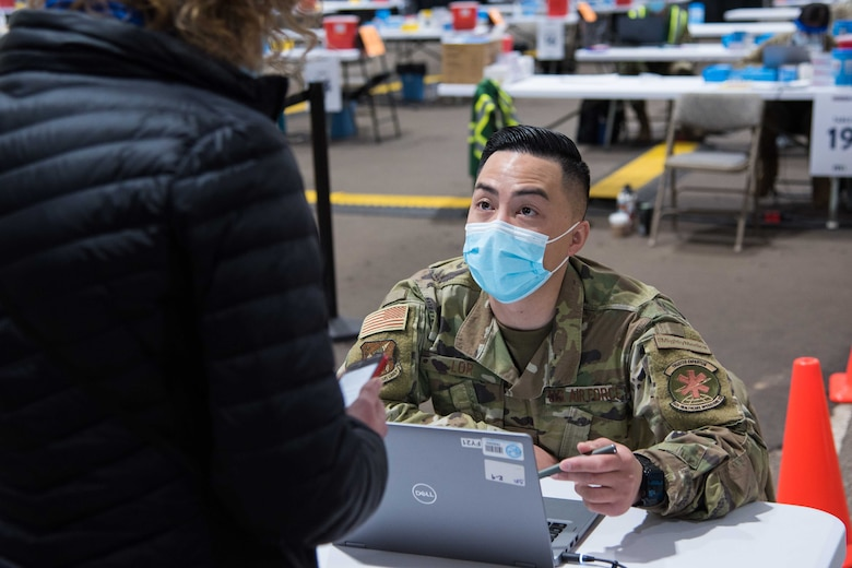 U.S. Air Force Senior Airman Peter Lor, 92nd Medical Group pharmacy technician, collects patient information before a COVID-19 vaccine is administered April 27, 2021, at the Community Vaccination Center (CVC) in St. Paul, Minnesota. The CVC welcomes the St. Paul community to receive free COVID-19 vaccines. U.S. Northern Command, through U.S. Army North, remains committed to providing continued Department of Defense support to the Federal Emergency Management Agency as part of the whole-of-government response to COVID-19. (U.S. Air Force photo by Senior Airman Alexi Bosarge)