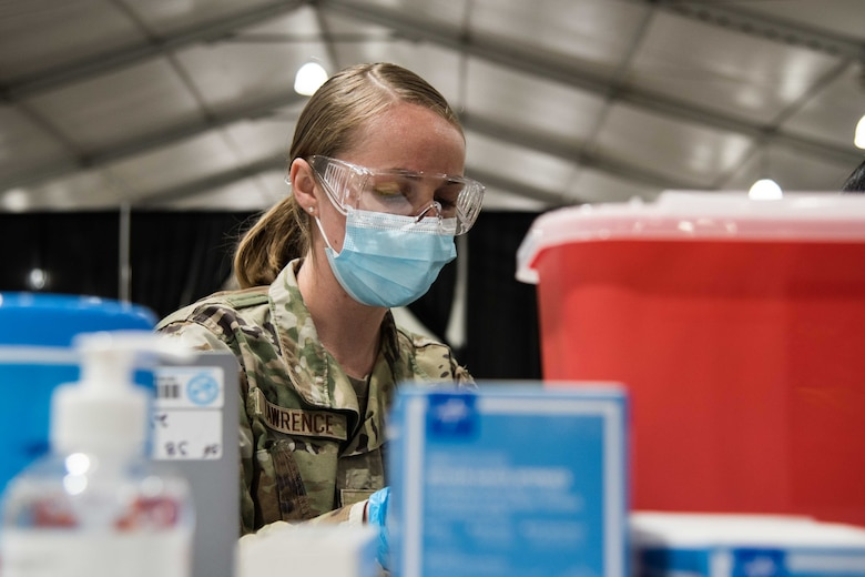 U.S. Air Force Senior Airman Daschia Lawrence, 92nd Healthcare Operation Squadron medical technician, prepares equipment for a COVID-19 vaccine April 27, 2021, at the Community Vaccination Center (CVC) in St. Paul, Minnesota. The total-force members include the U.S. Air Force, U.S. Army and U.S. Coast Guard from 24 bases across the country supporting the CVC. (U.S. Air Force photo by Senior Airman Alexi Bosarge)