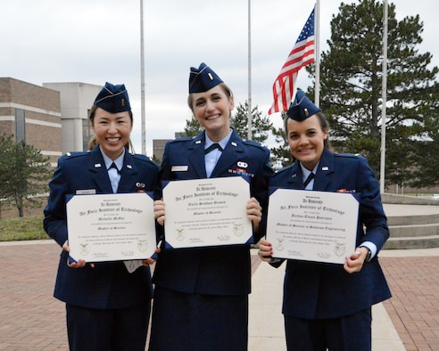 Second Lts. Michelle McGee, Emily Graves and Jordan Peterson display their Master of Science diplomas following the March 25 commencement ceremony at the Air Force Institute of Technology.  The Higher Learning Commission reaffirmed AFIT's degree-granting post-secondary education accreditation for the maximum 10 year period in March.