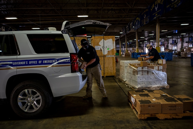 A man moves boxes from a truck to a pallet.