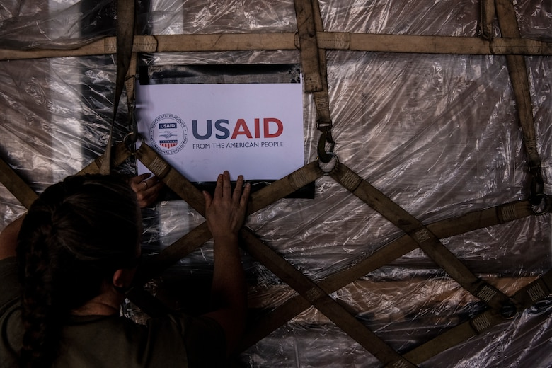 """A sign is being placed on a pallet and the sign says """"USAID, from the American people."""""""