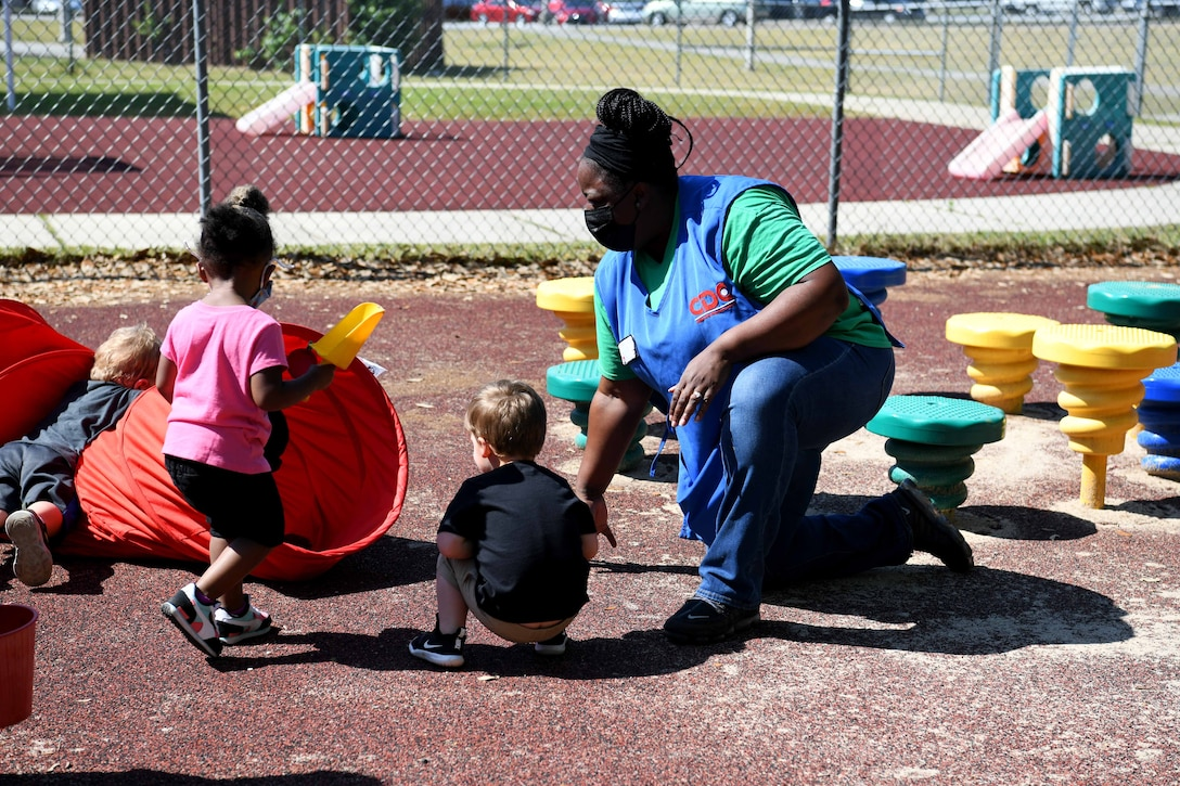 lady kneeling on playground with pre-kids